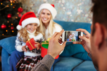 Cropped view of father taking photo on mobile phone of his wife and daughter in Santas hat, selective focus on phone Stock Photo