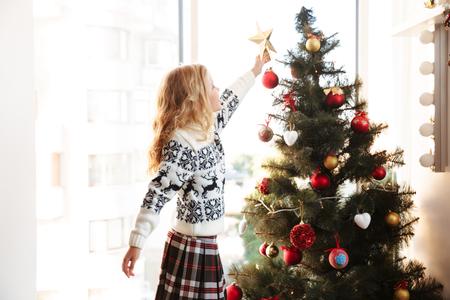 クリスマスツリーの上に星を置くニットセーターでかわいい女の子 写真素材