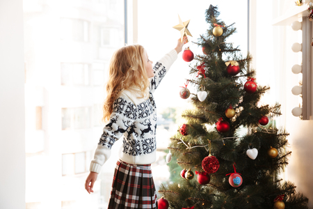 Cute little girl in knitted sweater placing star on the top of Christmas tree Stock Photo