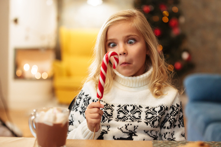 Close-up portrait of curious little girl holding and looking at big candy cane while sitting at the table on Christmas morning  Stock Photo