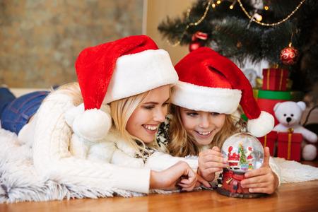 彼女の母親と一緒に床に横たわっている間、雪のボールのおもちゃで遊んで幸せな少女のクローズアップ 写真素材