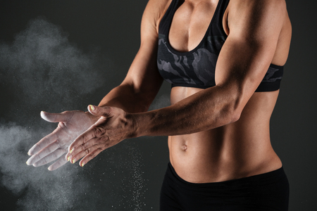 Cropped image of a muscular sportswoman clapping hands with talc powder before work out isolated over gray background Stock Photo