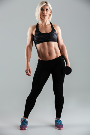Full length portrait of a adult muscular sportswoman holding heavy dumbbell isolated over gray background