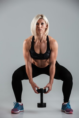 Full length portrait of a concentrated muscular adult sportswoman doing squats with a heavy dumbbell isolated over gray background