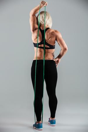 De volledige lengte van vrouwelijke atleet in sport draagt uitrekkende hand met elastisch die rubber, op witte achtergrond wordt geïsoleerd