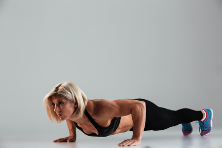 Full length portrait of a strong muscular adult sportswoman doing push-ups isolated over gray background Stock Photo