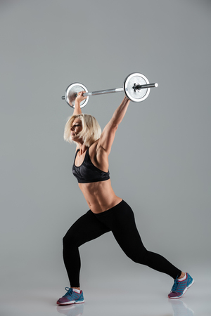 Full length portrait of a confident strong muscular adult sportswoman standing and lifting a barbell isolated over gray background Stock Photo