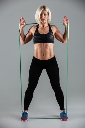 Foto integrale della donna seria di forma fisica che allunga con gomma elastica, esaminante macchina fotografica, isolata su fondo bianco