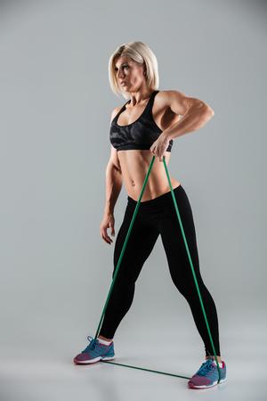Foto van het zijaanzicht van sportenvrouw die met weerstandsband uitoefent die, op witte achtergrond wordt geïsoleerd
