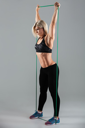 탄성 고무, 흰색 배경에 격리와 스트레칭 제기 무기와 건강 한 스포츠 여자의 측면보기 사진