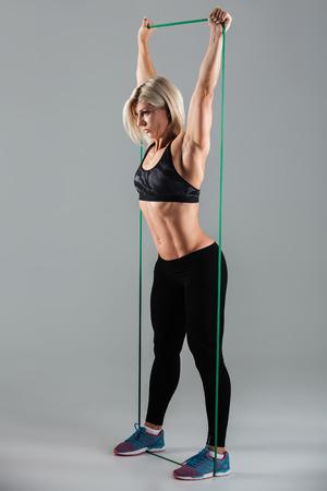 Zijaanzichtfoto van gezonde sportenvrouw met opgeheven wapens die zich met elastisch die rubber uitrekken, op witte achtergrond wordt geïsoleerd Stockfoto