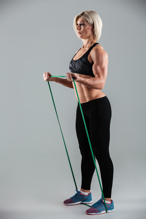 Full length photo of strong sports woman exercising with resistance band, looking aside, isolated on white background