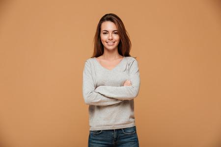 El retrato de la mujer morena hermosa sonriente que mira la cámara, colocándose con cruzado entrega el fondo beige Foto de archivo - 89489053