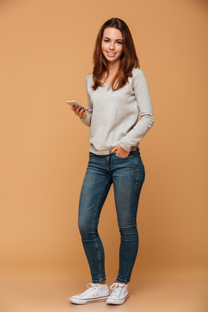 Full length portrait of smiling beautiful woman in casual wear standing with hand in the pocket, holding smartphone, looking at camera, isolated on beige background Banco de Imagens