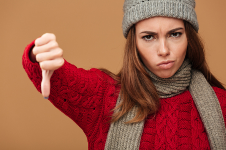 Close-up portrait of upset woman in winter clothes showing thumb down gesture, looking at camera over beige background