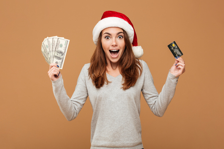 Photo of excited shocked caucasian lady wearing christmas hat standing isolated holding money and credit card. Looking camera.