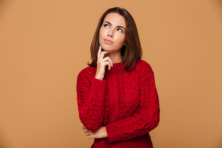 Photo of charming thoughtful young pretty girl in red sweater touching her chin, looking aside, isolated on beige background Stock Photo