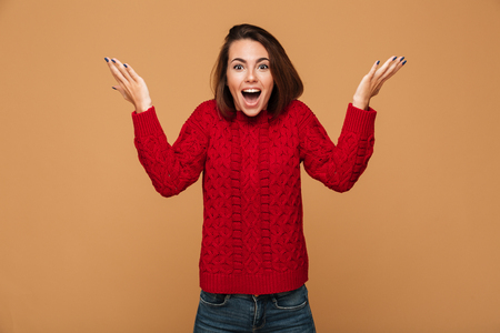 Amazed young attractive brunette woman in warm knitted sweater standing with raised hands, looking at camera, isolated over beige background Stock Photo