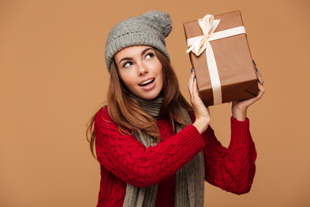Young charming woman in red knitted sweater holding gift box, looking aside, isolated on beige background Stock Photo