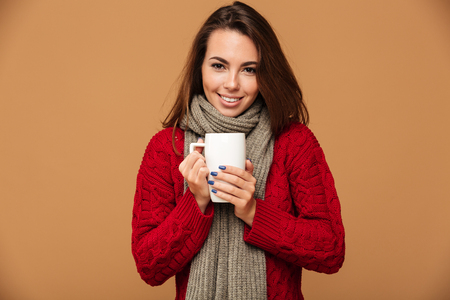 Picture of happy caucasian lady dressed in sweater and wearing scarf standing isolated. Looking camera drinking hot tea. Stock Photo