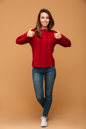 Full length portrait of smiling brunette woman in red knitted sweater and jeans showing thumbs up gesture with two hands, looking at camera, isolated on beige background Stock Photo