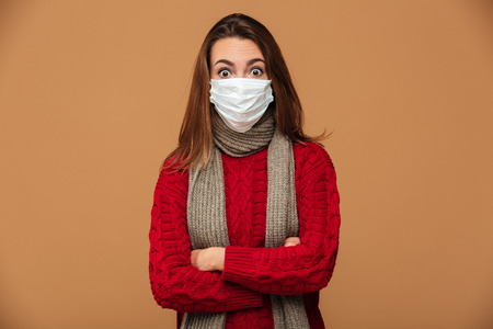 Surprised young woman in protective mask standing with crossed hands, looking at camera, isolated on beige background