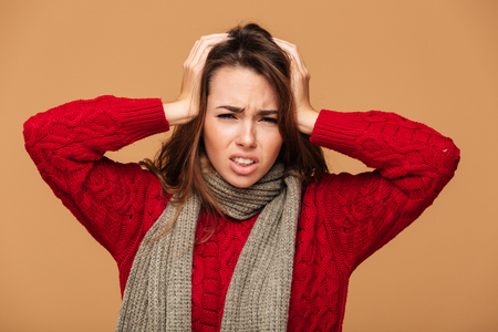 Close-up portrait of sick young brunette woman holding her head, looking at camera, isolated on beige background