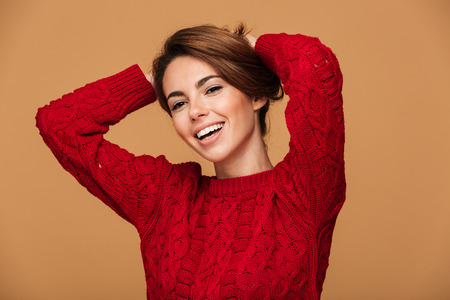 Close-up portrait of happy young brunette woman making hairstyle, looking at camera, isolated on beige background Stock Photo