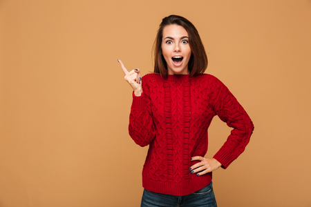 Happy young woman with opened mouth pointing with finger up, looking at camera, isolated on beige background Stock Photo
