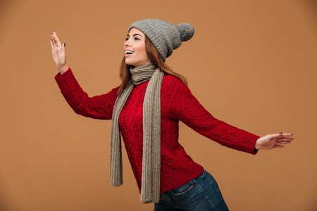 Happy young woman in red knitted sweater and gray hat posing over beige background