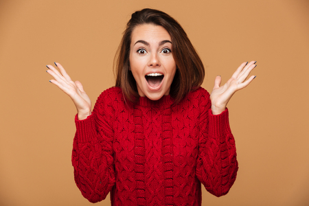 Close-up shot of young surprised brunette woman standing with opened palms, over beige background