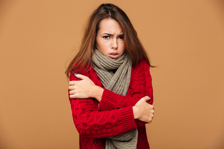 Portrait of sad freezing brunette woman in red knitted sweater shivering while hugging herself, looking at camera, isolated on beige background