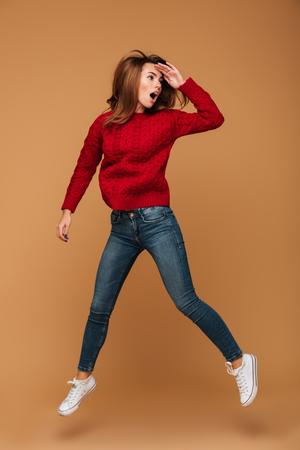 Volledig lengteportret van verbaasde mooie donkerbruine vrouw die in rode gebreide sweater over beige achtergrond springt, die opzij eruit ziet Stockfoto
