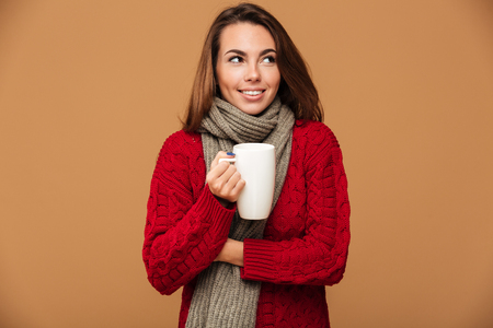 Image of cheerful caucasian lady dressed in sweater and wearing scarf standing isolated. Looking aside drinking hot tea.