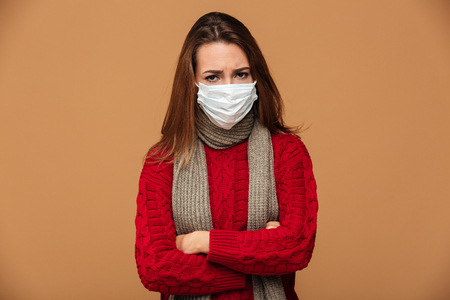 Sick woman in protective mask standing with crossed hands, looking at camera, isolated on beige background 版權商用圖片