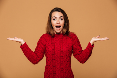 Amazed young pretty woman in red knitted sweater standing with opened palms, looking at camera, isolated on beige background Stock Photo