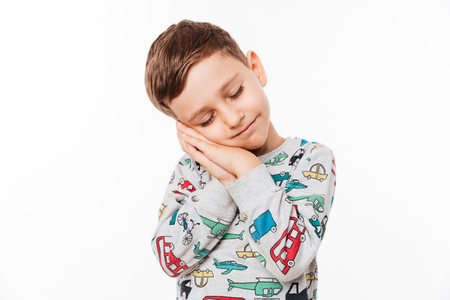 Portrait of a cute little kid standing with hands sealed pretending he is sleeping isolated over white background