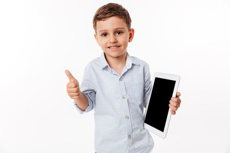 Portrait of a cheerful cute little kid holding blank screen tablet computer and showing thumbs up gesture isolated over white background Фото со стока