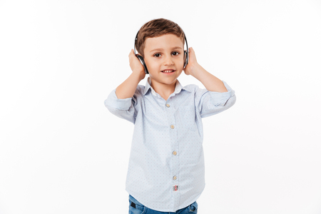 Portrait of a cute little kid in headphones listening to music and looking at camera isolated over white background Stock Photo