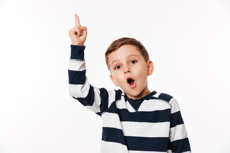 Portret van een opgewonden slim klein jong geitje die vinger benadrukken die en camera bekijken over witte achtergrond wordt geïsoleerd