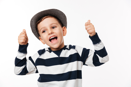 Portrait of an excited cute little kid in a hat showing thumbs up gesture with two hands and looking away isolated over white background Stock Photo
