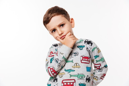 Portrait of a pensive cute little kid standing with hand on chin isolated over white background Stock Photo