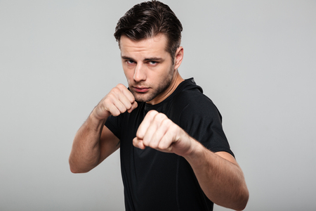 Close up portrait of a strong fit sportsman standing in a boxing position isolated over gray background Stock Photo