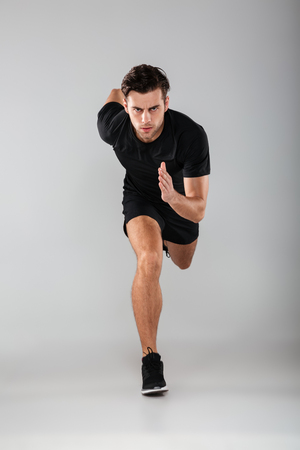 Photo of strong young sports man running isolated over grey wall background. Looking camera.