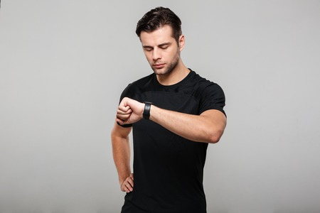 Portrait of a young sportsman looking at his wristwatch isolated over gray background Banco de Imagens