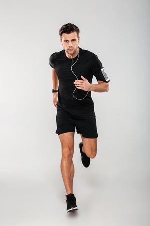 Full length portrait of a serious young man athlete in earphones listening to music while running isolated over gray background