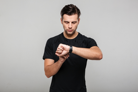 Portrait of a focused young sportsman adjusting his wristwatch isolated over gray background Banco de Imagens