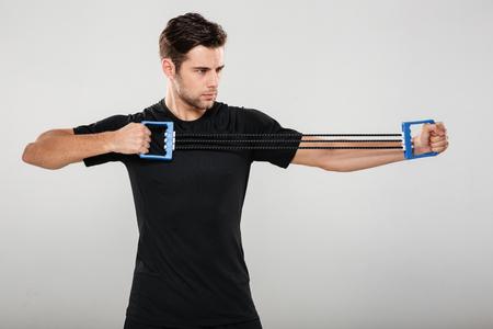 Portret van een zekere gezonde sportman die oefening met expander doen die over grijze achtergrond wordt geïsoleerd