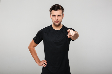 Portrait of a young confident sportsman pointing finger at camera isolated over gray background Stok Fotoğraf
