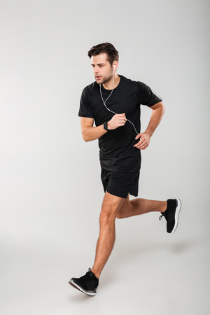 Side view full length portrait of a confident young man athlete in earphones listening to music while running isolated over gray background